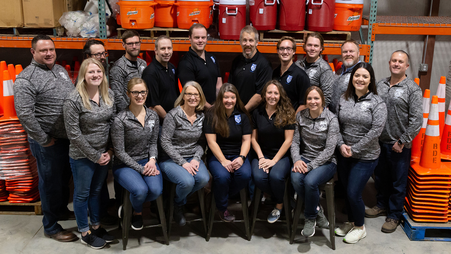 Race Day Events' staff photo; their team standing in front of race equipment like traffic cones and gatorade coolers.