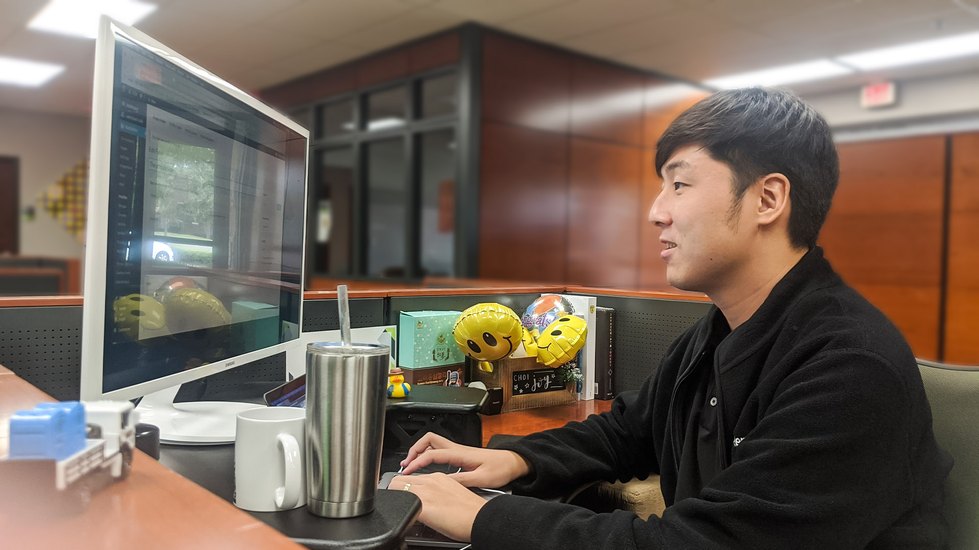 Thomas Choi works at his desk in the office.