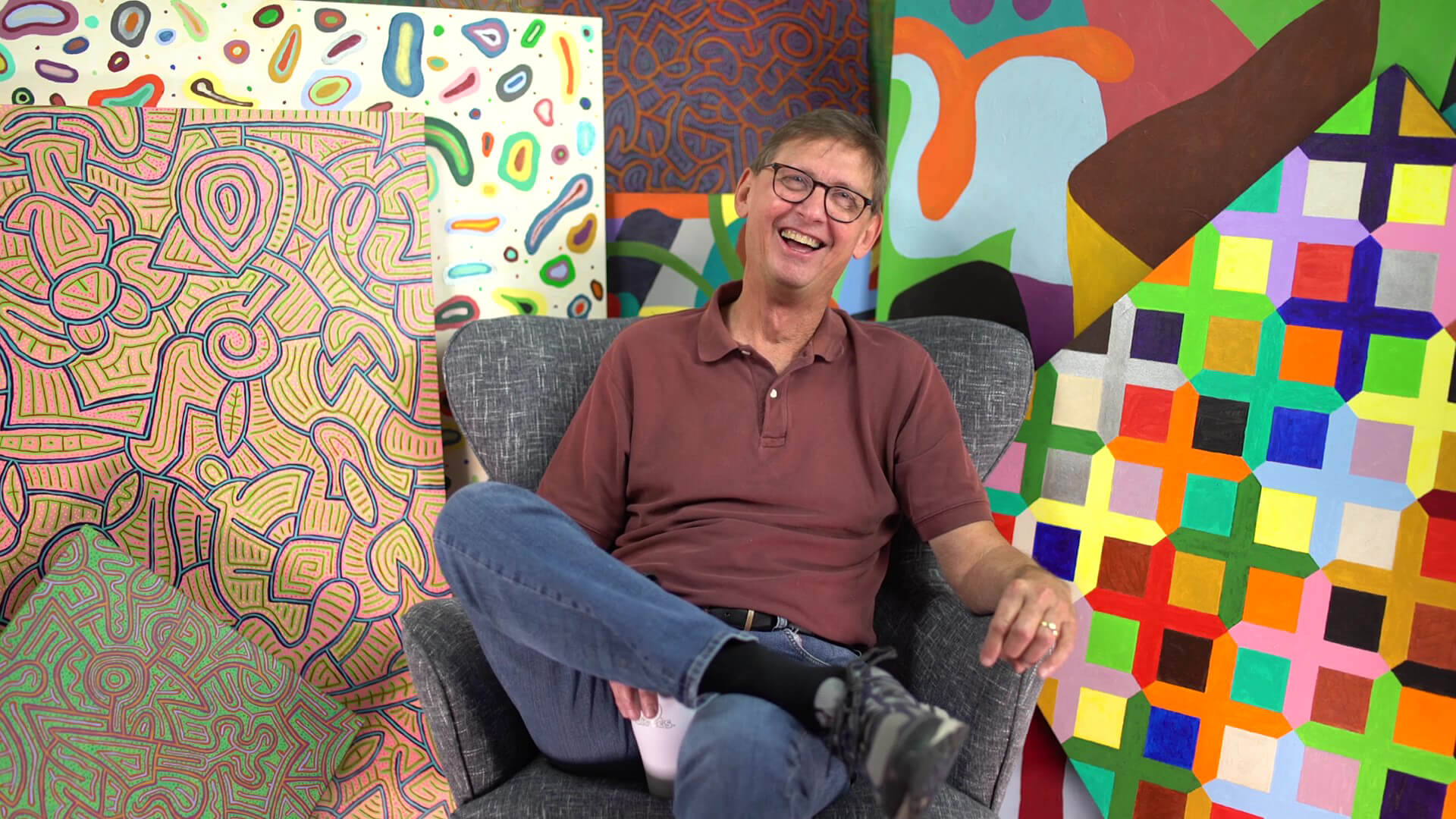 Earl Sherman sits in a chair among his art and laughs.